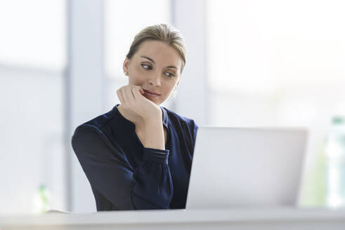 Businesswoman using laptop at desk in office - BMOF00132
