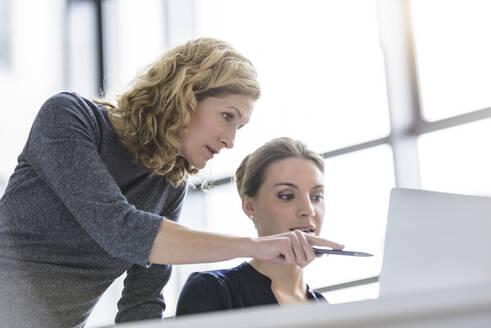 Two women working on laptop in office - BMOF00135