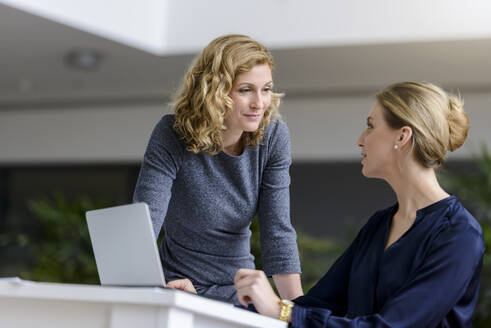 Two women talking at desk in office - BMOF00138