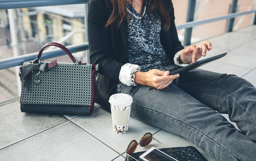 Midsection of woman using tablet computer while sitting on footbridge - CAVF70985
