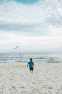 Rear view of boy running at Panama City Beach against cloudy sky - CAVF71241
