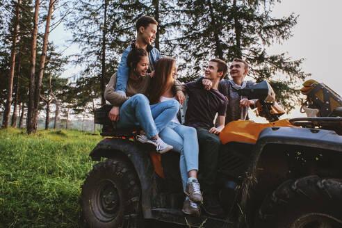 Friends sitting on quadbike at grassy field - CAVF71256