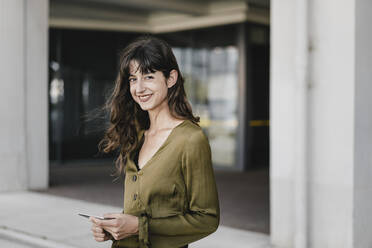 Portrait of smiling brunette woman holding smartphone - KNSF06974