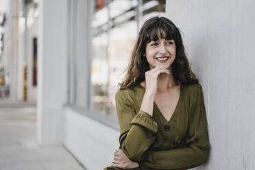 Portrait of smiling brunette woman leaning on a wall, looking sideways - KNSF06977