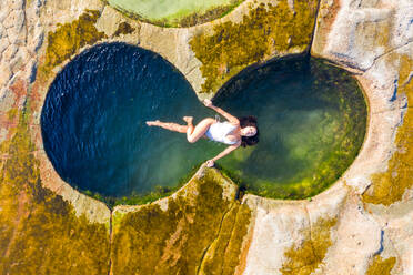 Aerial view of an attractive woman floating at figure eight pools at Sydney's Royal National Park, Australia. - AAEF06102