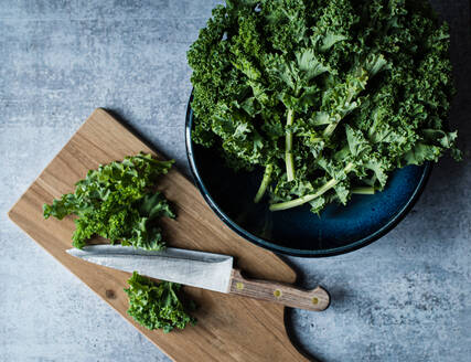 Top view of bowl of kale, cutting board with knife and chopped kale. - CAVF71599
