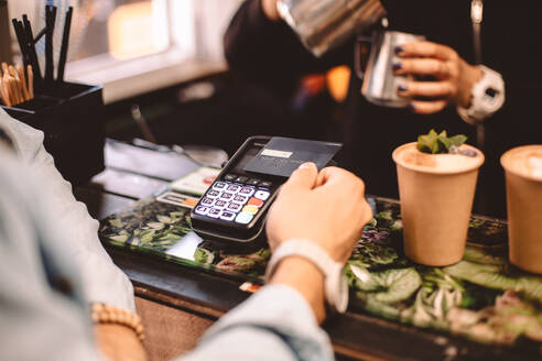 Customer making payment with credit card standing at checkout counter - CAVF71641