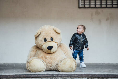 A little boy playing with a giant teddy bear. - CAVF71746