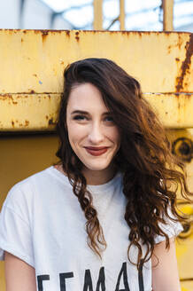 Portrait of happy millennial woman with curly long hair in the street - CAVF71851