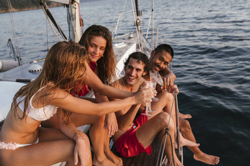 Friends toasting with champagne on sailboat, Italy - CUF54188