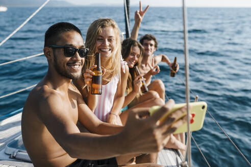 Friends taking selfie on sailboat, Italy - CUF54212