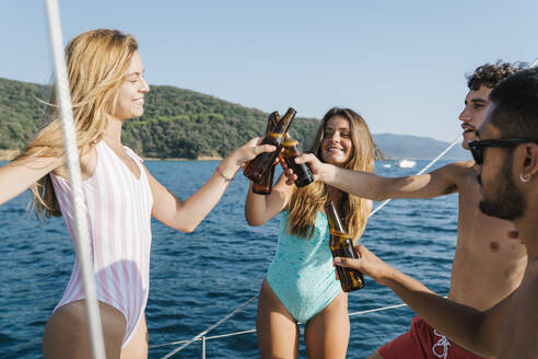 Friends toasting with beer on sailboat, Italy - CUF54218