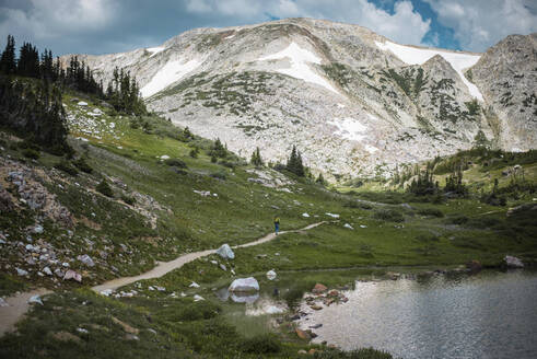Mid distance view of hiker on dirt road against Medicine Bow Mountains - CAVF72476