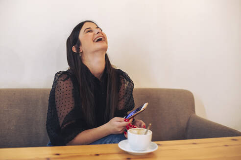 Young woman sitting in a cafe, holding smartphone and laughing - ACPF00643