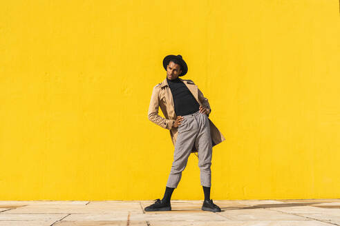 Young man dancing in front of yellow wall - AFVF04528