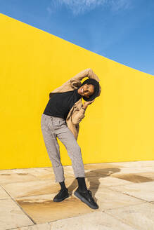 Young man dancing in front of yellow wall - AFVF04537