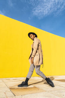 Young man dancing in front of yellow wall - AFVF04540