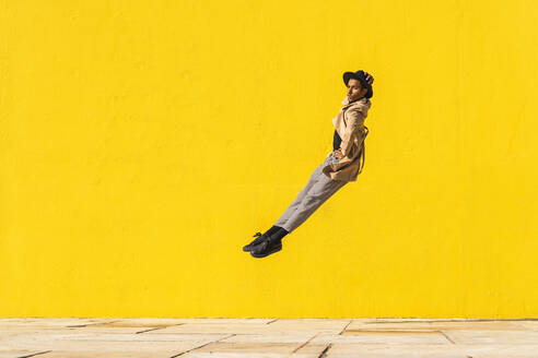 Young man dancing in front of yellow wall, jumping mid air - AFVF04546