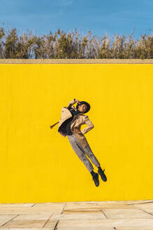 Young man dancing in front of yellow wall, jumping mid air - AFVF04549