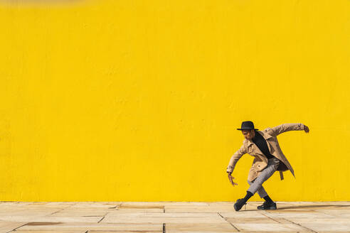 Young man dancing in front of yellow wall - AFVF04552
