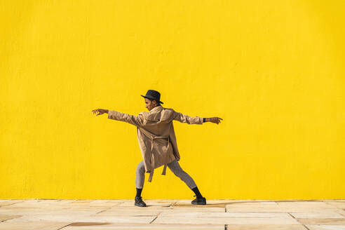 Young man dancing in front of yellow wall - AFVF04555
