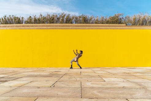 Young man dancing in front of yellow wall - AFVF04561