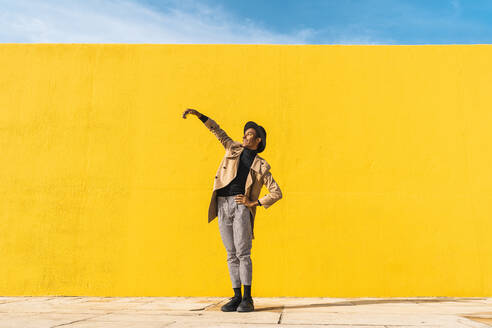 Young man dancing in front of yellow wall, taking selfies - AFVF04576