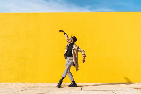 Young man dancing in front of yellow wall, taking selfies - AFVF04579