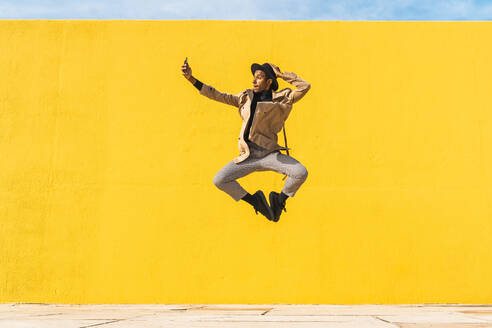 Young man dancing in front of yellow wall, taking selfies - AFVF04582