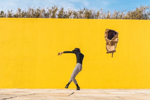 Young man dancing in front of yellow wall - AFVF04585