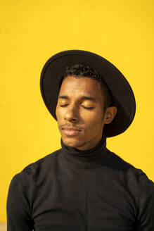 Portrait of young man, wearing black in front of yellow wall, eyes closed - AFVF04588