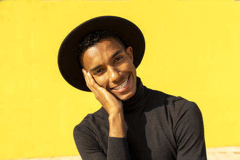 Portrait of young man, wearing black in front of yellow wall, hand on face - AFVF04591