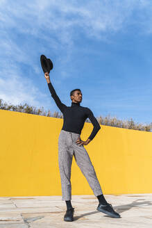 Young man with black hat, dancing in front of yellow wall - AFVF04594
