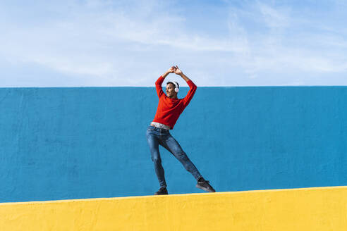 Young man with headphones, listening music, dancing on yellow wall - AFVF04603