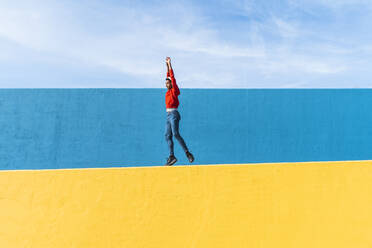 Young man with headphones, listening music, dancing on yellow wall - AFVF04606