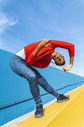 Young man with headphones, listening music, dancing on yellow wall - AFVF04609
