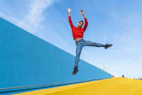 Young man with headphones, listening music, dancing on yellow wall - AFVF04612