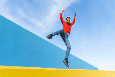 Young man with headphones, listening music, dancing on yellow wall - AFVF04615