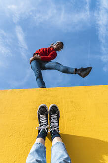 Young man with headphones, dancing for person, leaning on yellow wall - AFVF04618