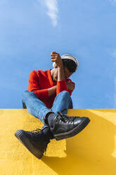Young man with headphones, sitting on yellow wall, listening music - AFVF04624