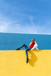 Young dancer sitting on yellow wall, listening music - AFVF04627