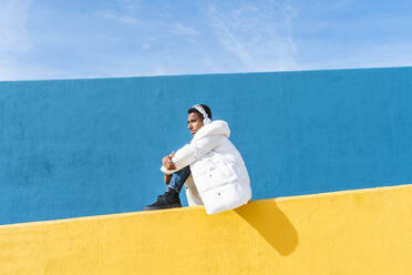 Young trendy man sitting on yellow wall, listening music - AFVF04630