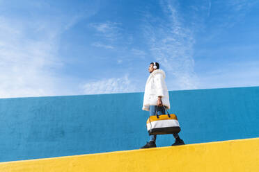 Young trendy man standing on yellow wall, listening music - AFVF04633