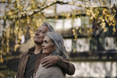 Affectionate senior couple in garden of their home in autumn - GUSF02973