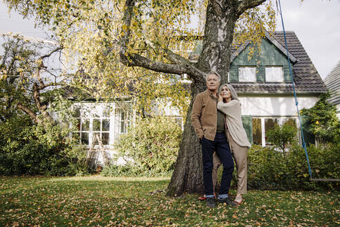 Senior couple in garden of their home in autumn - GUSF02982