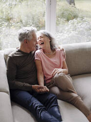 Happy senior couple relaxing on couch at home - GUSF03003