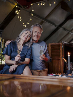 Portrait of senior couple having a candlelight dinner on a boat in boathouse - GUSF03027