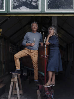 Senior couple in a boathouse with glass of champagne - GUSF03030