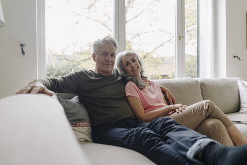 Portrait of senior couple relaxing on couch at home - GUSF03036