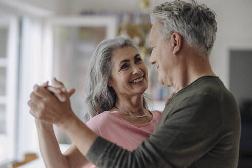 Happy senior couple dancing in living room at home - GUSF03042